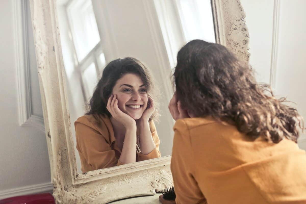 Усмиханто момиче в огледалото сутрин